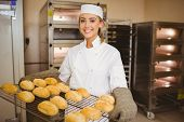 stock photo of bread rolls  - Baker smiling at camera holding rack of rolls in a commercial kitchen - JPG
