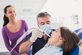 stock photo of suction  - Pediatric dentist examining young patient with a suction tube in dental clinic - JPG