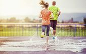 pic of rainy weather  - Young couple jogging on asphalt in rainy weather - JPG
