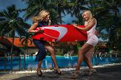 stock photo of bereavement  - Pretty girls with surfboard on a resort - JPG