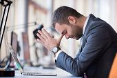 image of frustrated  - frustrated young business man working on laptop computer at office - JPG