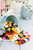 picture of jelly beans  - A blue tin bucket tipped over spilling jelly beans onto a table - JPG
