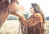 Picture of woman stroking horse.