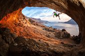 stock photo of cave  - Male rock climber climbing along a roof in a cave at sunset