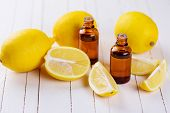 stock photo of essential oil  - Essential aroma oil with lemon on wooden background - JPG