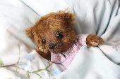 foto of pyjama  - Cute teddy bear in pink pyjama resting in the bed - JPG