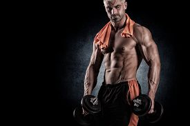 picture of human muscle  - with dumbbells over black background muscular - JPG