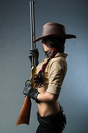 image of girls guns  - girl cowboy with a gun on a gray background - JPG