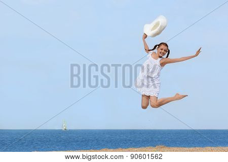 Cheerful Girl Jumping Over The Water At The Beach