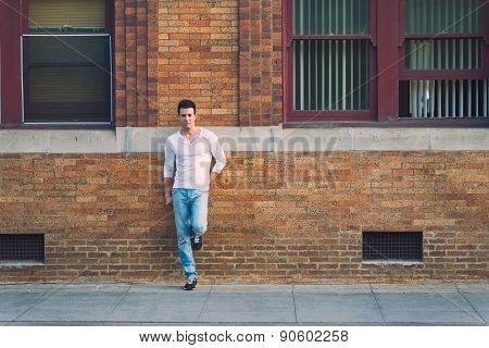 Stylish Casual Sexy And Serious Man Lean Back Brick Building.