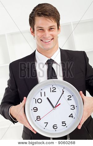 happy businessman holding clock