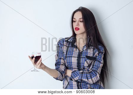 Brunette holding a glass of wine and looking at it
