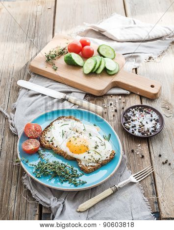 Breakfast set. Whole grain andwich with fried egg, vegetables and herbs on rustic wooden table, morn