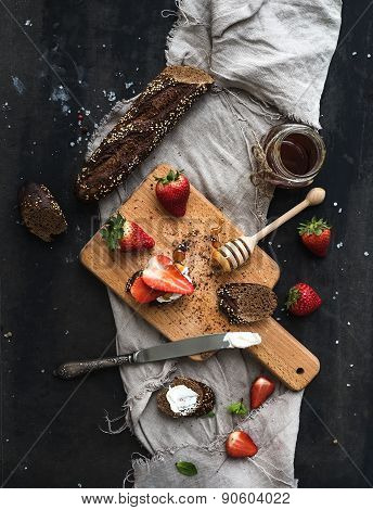 Breakfast set. Black baguette toasts with fresh strawberries, honey and mascarpone cheese on dark gr