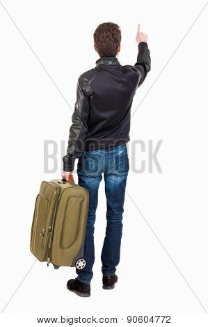 back view of  pointing man  with suitcase. brunette guy in a leather jacket pointing .  backside view of person.  Rear view people collection. guy with travel bag on wheels looking at something at top