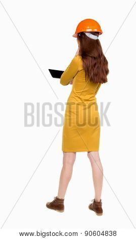 Backview of business woman in construction helmet stands and enjoys tablet or using a mobile phone. Standing young girl. Rear view people collection.   Girl dress in mustard works on a computer.