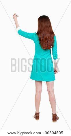 back view of writing beautiful woman. Young girl in dress. Rear view people collection.  backside view of person. Isolated over white background. Girl in dress and leather shoes draws on the wall