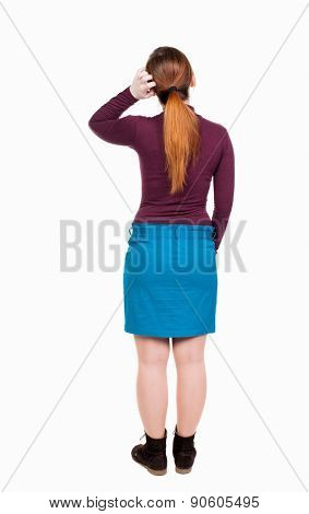 back view of standing young beautiful  woman.  girl  watching. Rear view people collection.  backside view of person.  Red-haired girl in a blue skirt touches the hair in thought.
