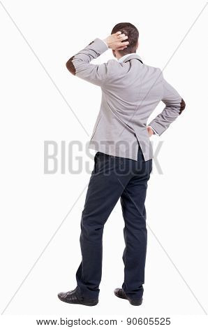 back view of standing business man. Young businessman scratches his head in amazement. Rear view people collection.  backside view of person.  Isolated over white background.