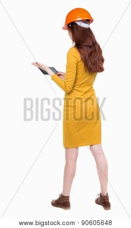 Backview of business woman in construction helmet stands and enjoys tablet or using a mobile phone. Standing young girl. Rear view people collection.   Young woman engineer working on the tablet.