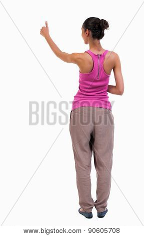 Back view of  curly woman thumbs up. Rear view people collection. backside view of person. Isolated over white background. slender blonde in a jeans shows the symbol of success or hitchhiking