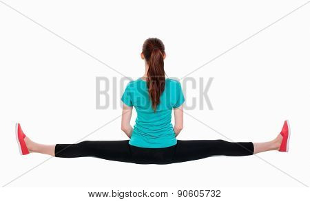 back view of standing young beautiful  woman in sport dress  involved in Pilates. Rear view people collection.    Isolated over white background. Sportswoman sitting on a longitudinal splits