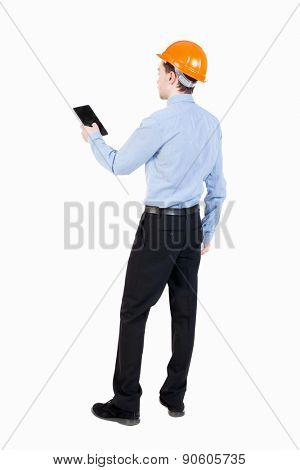 Backview of business man in construction helmet stands and enjoys tablet or using a mobile phone. Standing young guy. Businessman supervises construction.