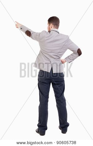 Back view of pointing business man. gesticulating young guy in black suit. Rear view people collection.  backside view of person. putting his hand on waist, other hand businessman showing up