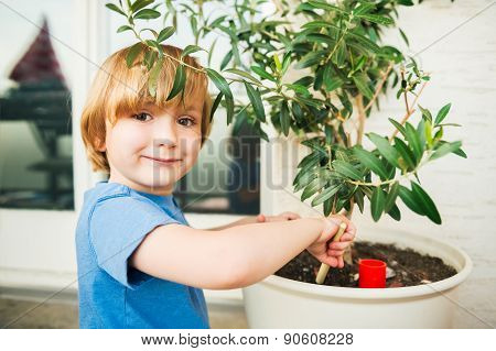 Cute little boy playing with garden tools on the balcony
