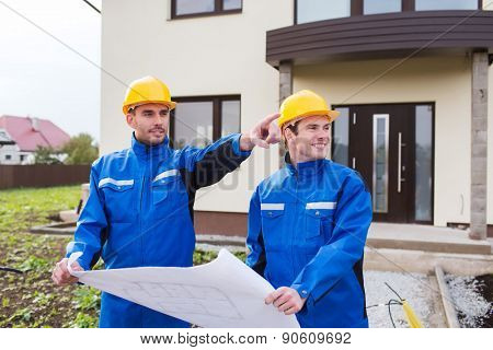 building, teamwork and people concept - two smiling builders in hardhats and overalls with blueprint pointing finger in front of house outdoors