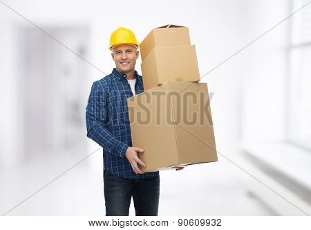 repair, building, construction, loading and delivery concept - smiling man or loader in helmet with cardboard boxes over room background