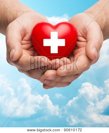 family health, charity and medicine concept - close up of male hands holding red heart with white cross over blue sky and clouds background