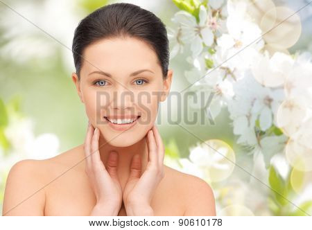 beauty, people and health concept - beautiful young woman touching her face and neck over green blooming garden background