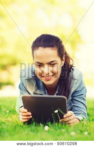 lifestyle, summer vacation, technology, leisure and people concept - smiling young girl with tablet pc computer lying on grass in park