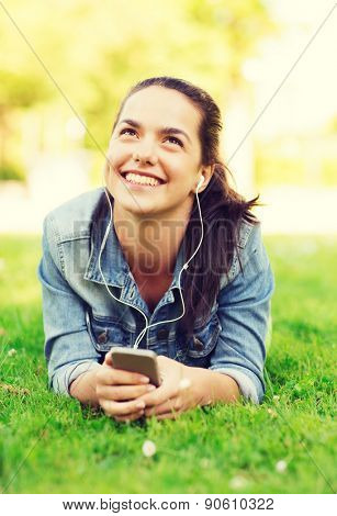 lifestyle, summer vacation, technology, leisure and people concept - smiling young girl with smartphone and earphones lying on grass