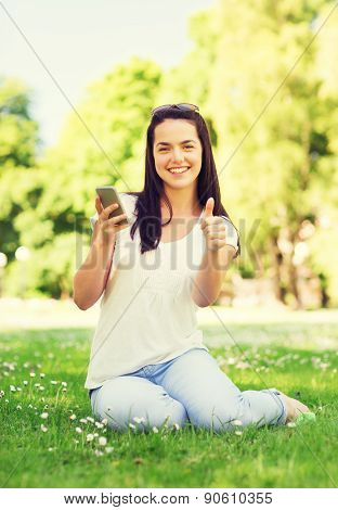 lifestyle, summer vacation, gesture, technology and people concept - smiling young girl with smartphone showing thumbs up in park