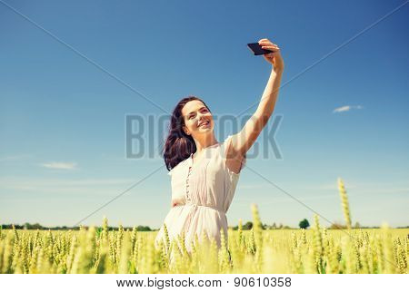 happiness, nature, summer, vacation and people concept - smiling young woman with smartphone on cereal field