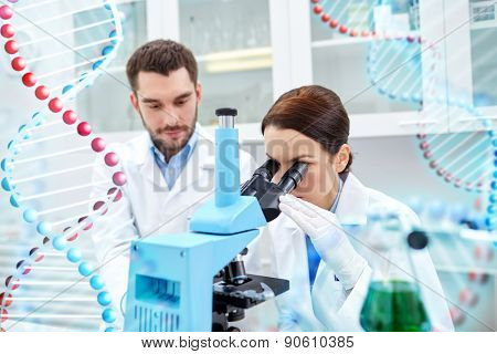 science, chemistry, technology, biology and people concept - young scientists looking to sample through microscope and making test or research in clinical laboratory over dna molecule structure