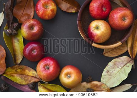 Autumn background with Red apples, yellow autumn leaves, limes on black dark background. Thanksgivin