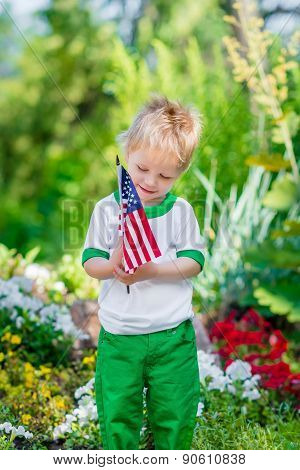 Smiling Little Boy With Blond Hair Holding American Flag And Looking At It In Sunny Park Or Garden