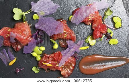 Red tuna sashimi on a slate plate.