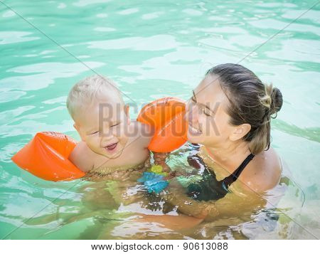 Baby and mother in swimming pool