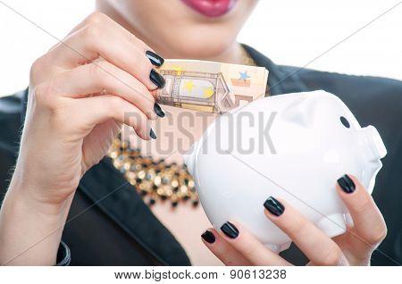 Close-up shot of a female hand put 50 euro banknote in a piggy bank