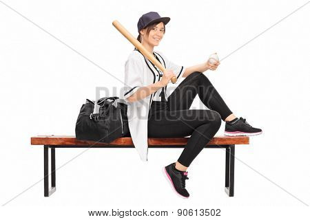 Female baseball professional holding a baseball bat seated on a bench with a black sports bag beside her isolated on white background