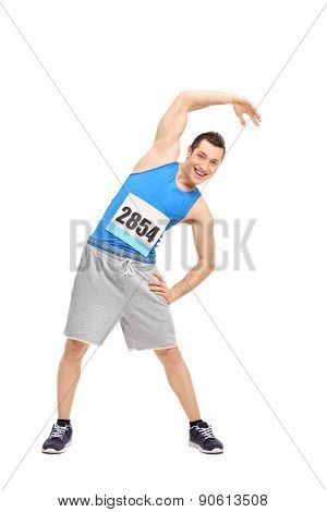 Full length portrait of a young male runner in a blue tank top doing stretching exercise and looking at the camera isolated on white background