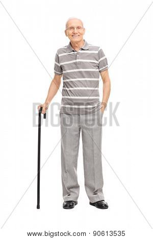 Full length portrait of an old man in a casual polo shirt holding a cane and posing isolated on white background