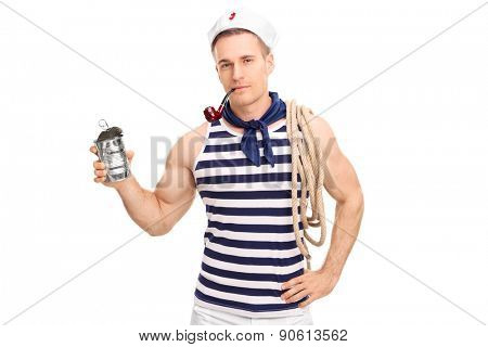 Young male sailor smoking tobacco from a pipe and holding an empty food can isolated on white background