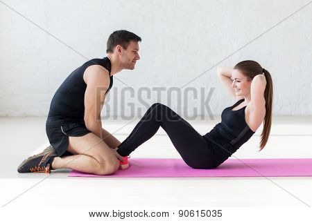 woman doing abdominal crunches press exercise on the mat with her sports male trainer in gym side vi