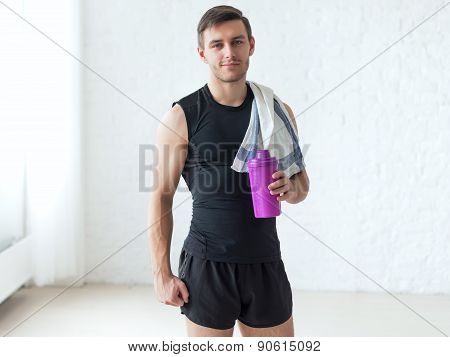 Portrait of a athletic man after doing exercises sportsman holding towel and shaker protein cocktail