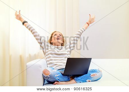 Young woman sitting on a sofa with her laptop computer raised her hands in the air, expressing happiness and success.